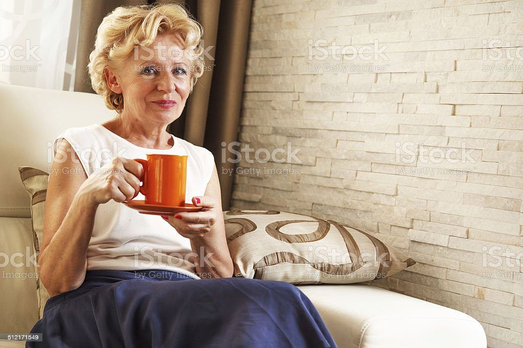 Beautiful senior woman holding cup, at home stock photo