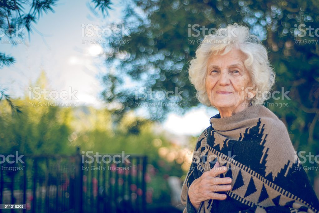 Beautiful Senior Woman Outdoors Wrapped in Alpaca Shawl stock photo