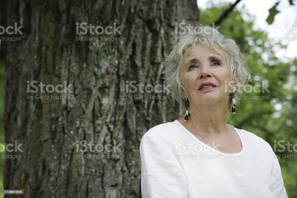 Beautiful Senior Woman Outside in Nature- Concerned Look Beside Tree royalty-free stock photo