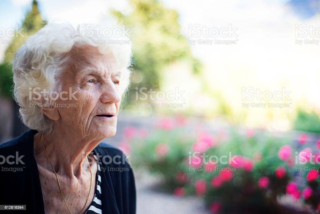 Beautiful Senior Woman Relaxing Outdoors in Back Yard stock photo