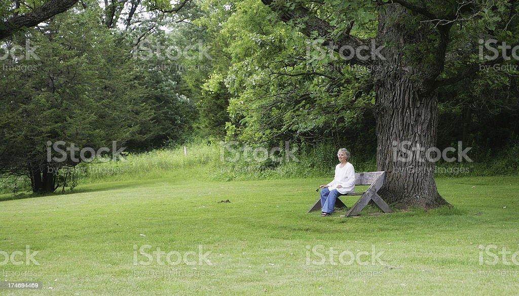 Beautiful Senior Woman Sitting Under Oak Tree royalty-free stock photo
