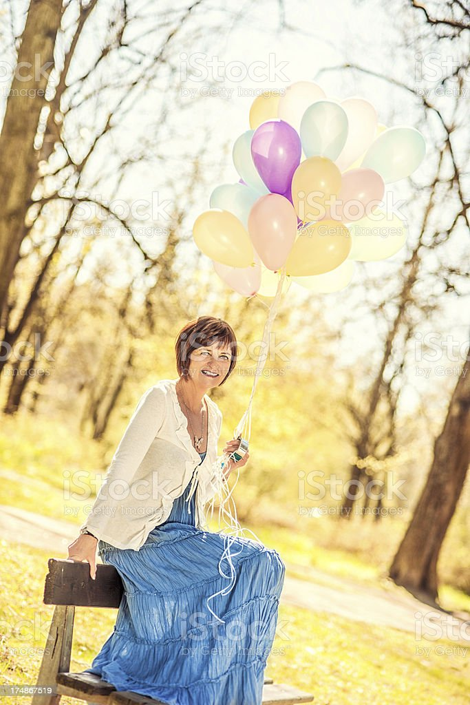 Beautiful senior woman sitting with ballons royalty-free stock photo