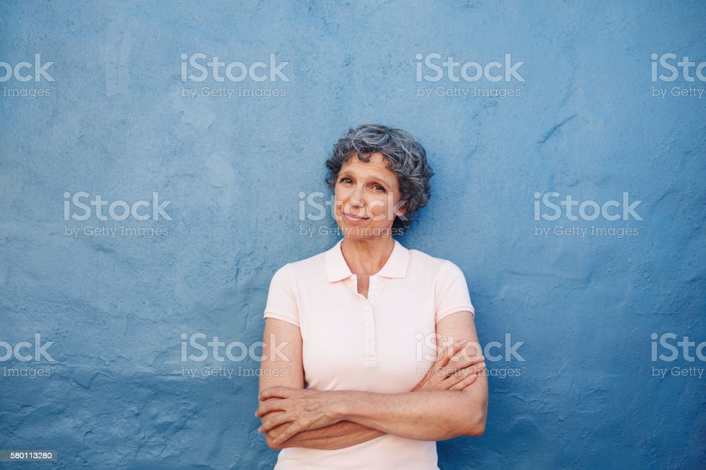 Beautiful senior woman standing with her arms crossed stock photo