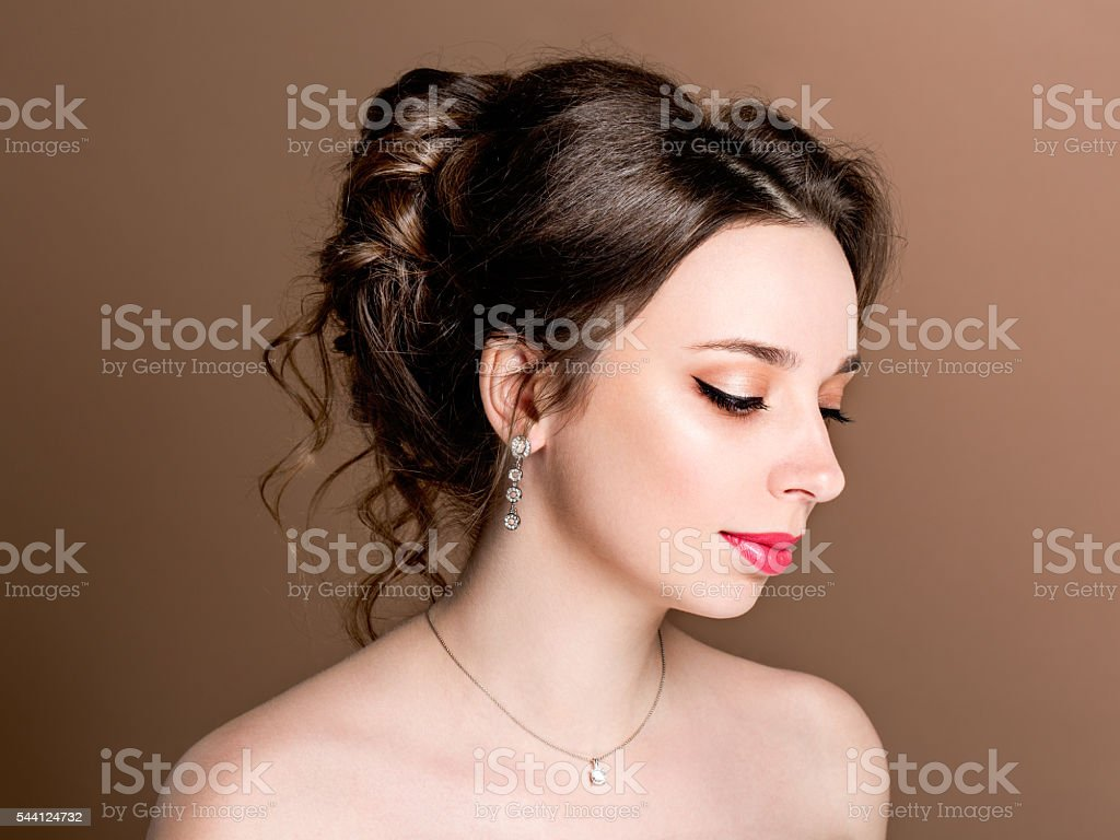Beautiful sensual brunette with elegant hairstyle.Beauty wedding hairstyle. Bride. stock photo