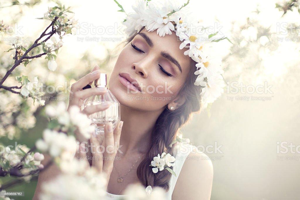 Beautiful sensual woman applying perfume stock photo