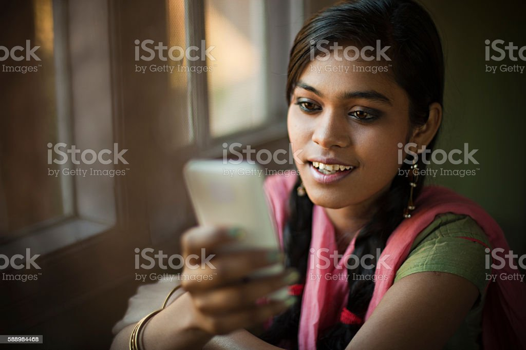 Beautiful serene Indian girl reading SMS sitting near window. stock photo