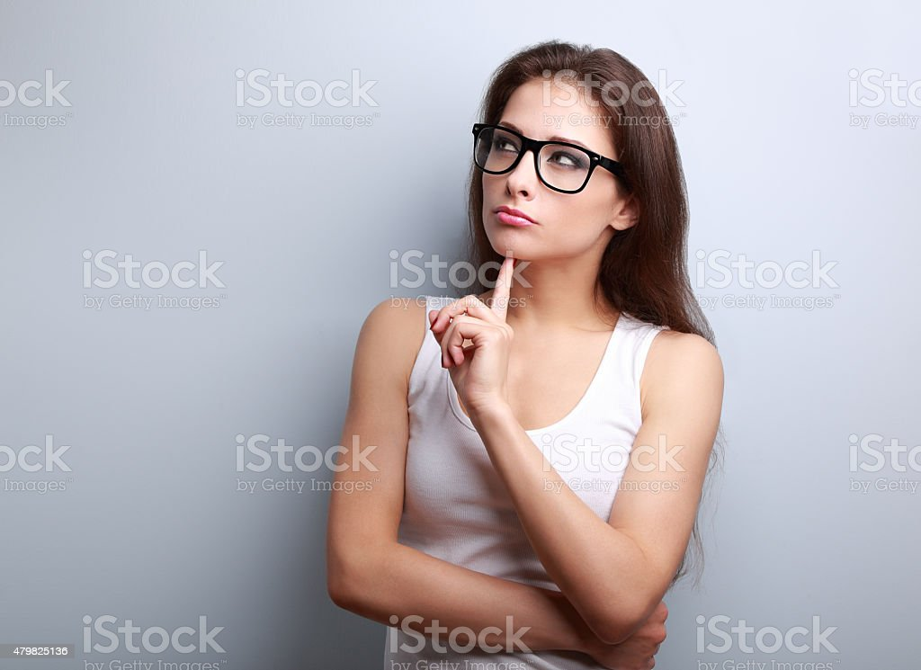 Beautiful serious thinking young woman looking up on empty copy stock photo