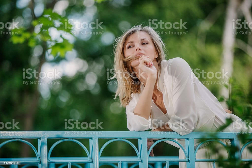 Beautiful serious woman leaning at handrails stock photo