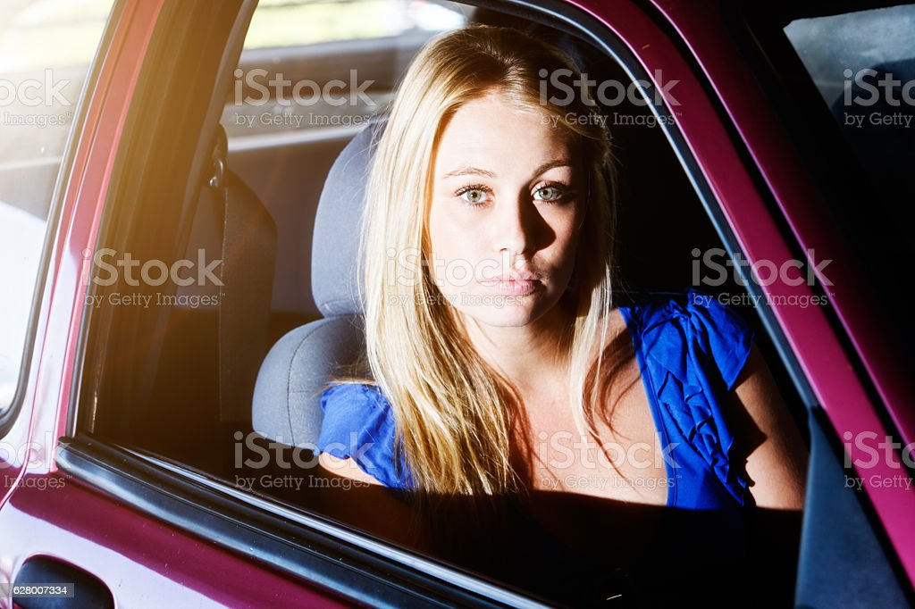 Beautiful, serious-looking, vulnerable blonde sitting in front seat of car stock photo