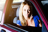 Beautiful, serious-looking, vulnerable blonde sitting in front seat of car