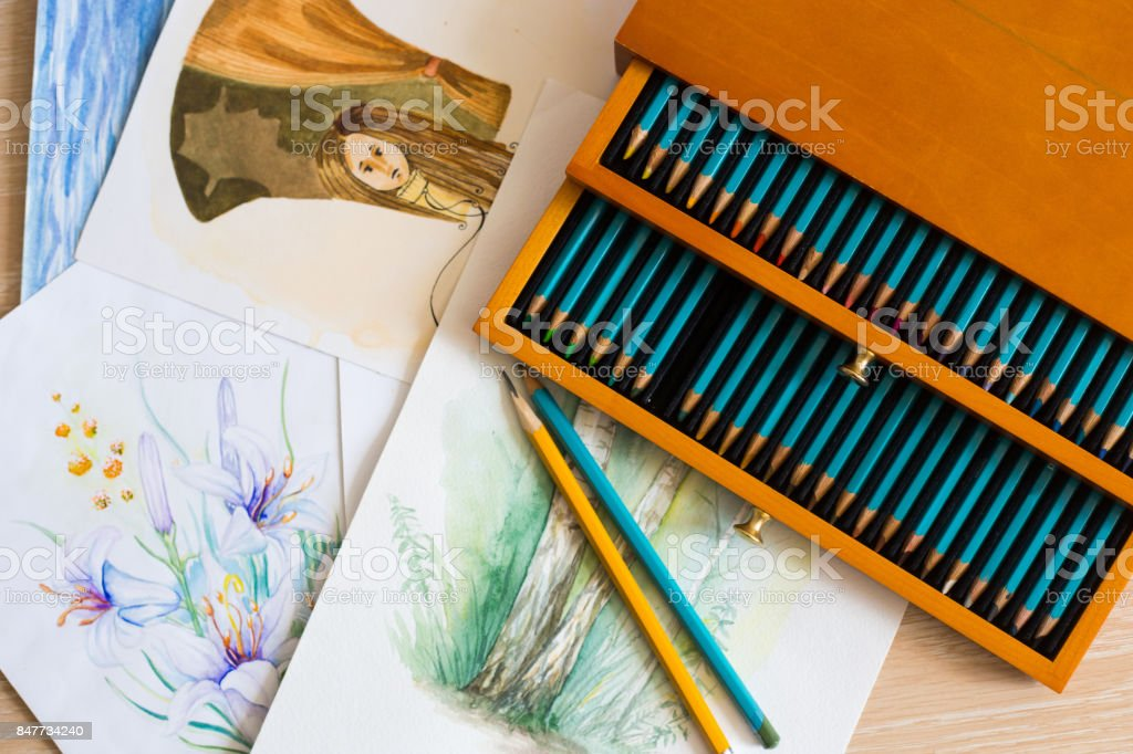 Beautiful set of watercolor paintings and luxury box of aquarelle pensils stock photo