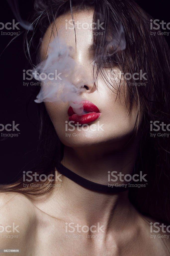 Beautiful sexy brunette girl with bright makeup, red lips, smoke stock photo