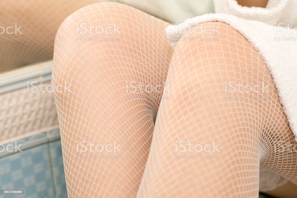 beautiful sexy female legs in white stockings stock photo