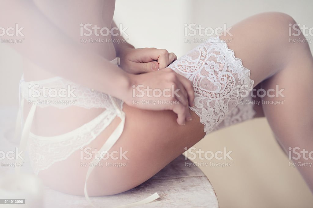 Beautiful sexy lady in elegant white panties and stockings stock photo