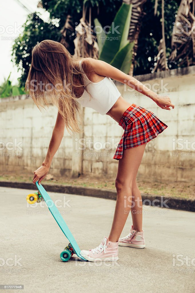 beautiful sexy young lady in erotic mini skirt with skateboard stock photo