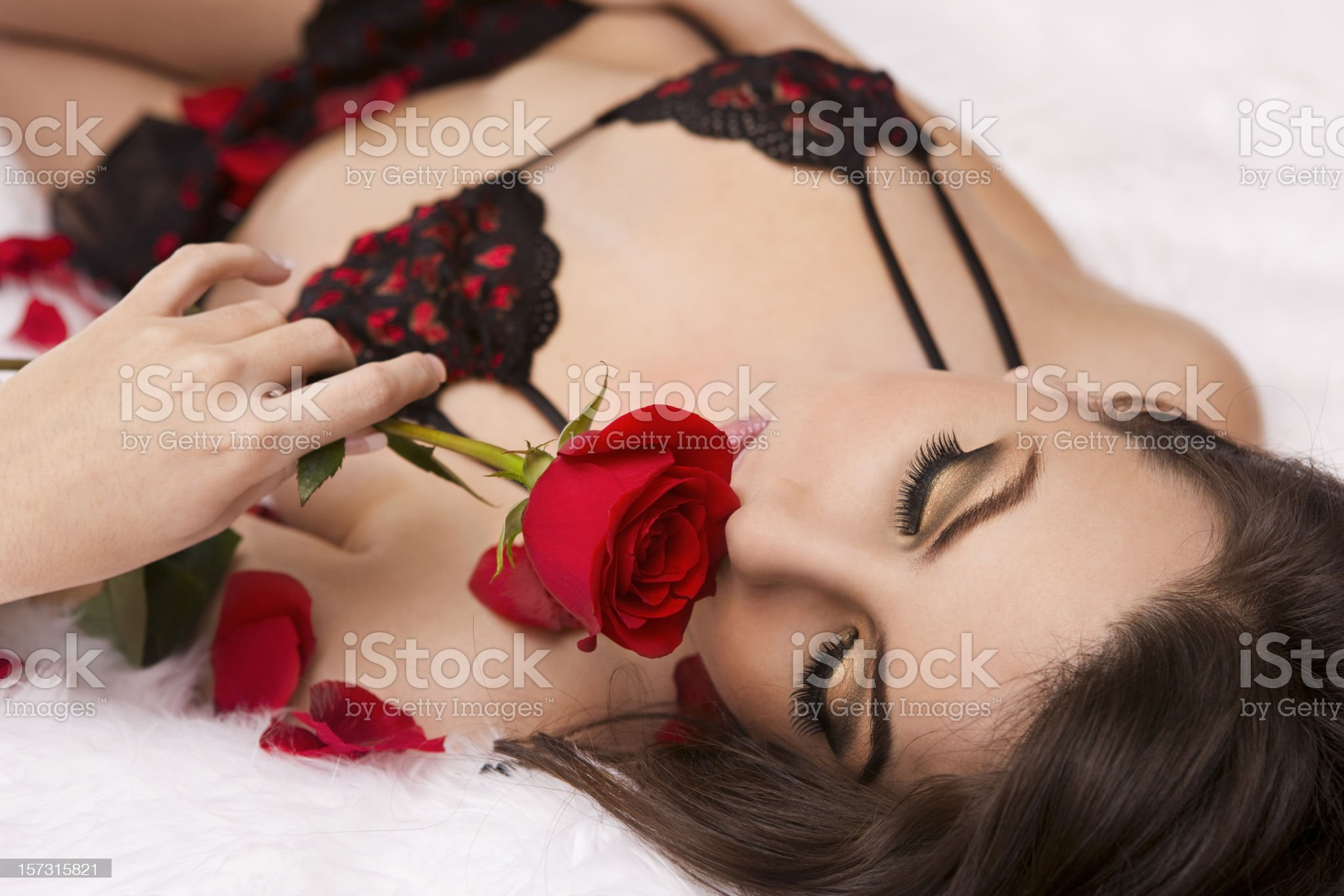 Beautiful, Sexy Young Woman in Valentines Lingerie Smelling Single Rose royalty-free stock photo