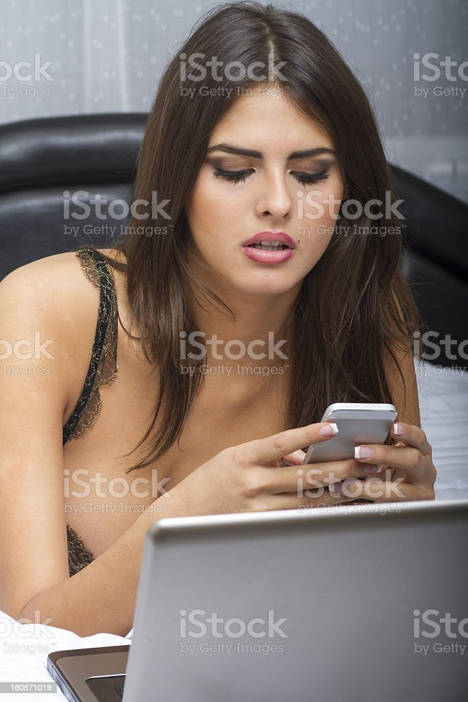 Beautiful Sexy Young Woman Wearing Lingerie, in Bed Checking Phone royalty-free stock photo