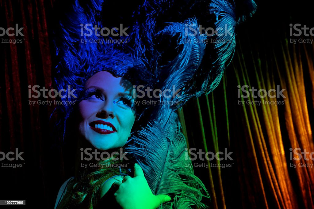 Beautiful showgirl backstage. She wears a blue costume with feathers. stock photo