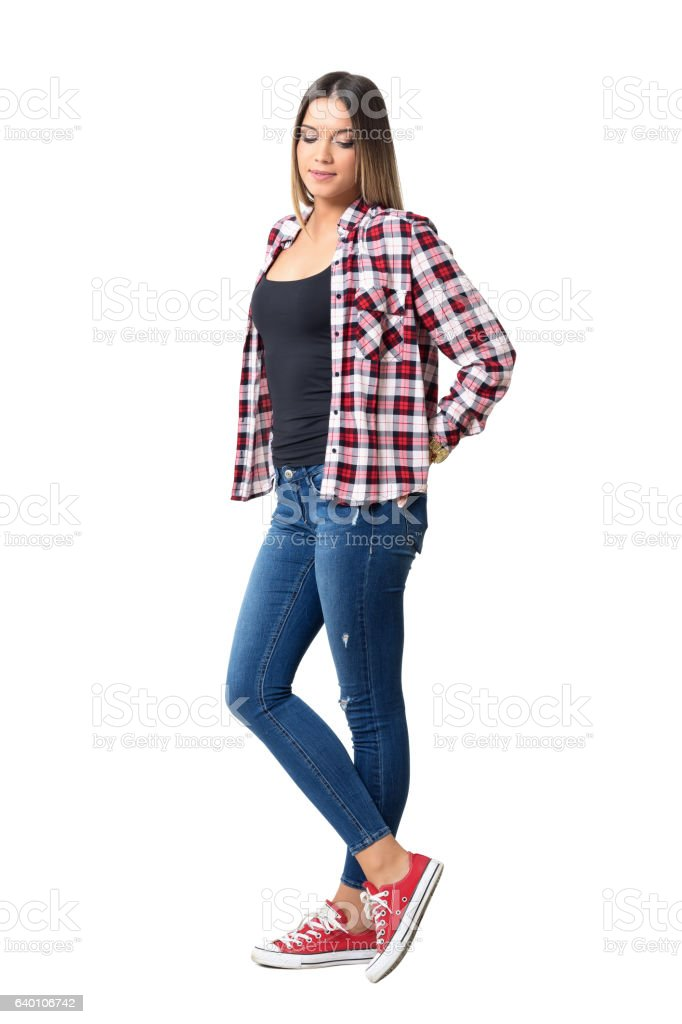 Beautiful shy casual girl wearing jeans and sneakers looking down stock photo