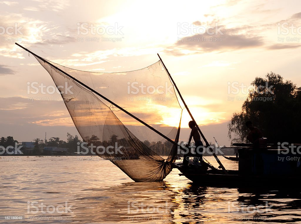 Beautiful silhouette of fishing boat with net stock photo