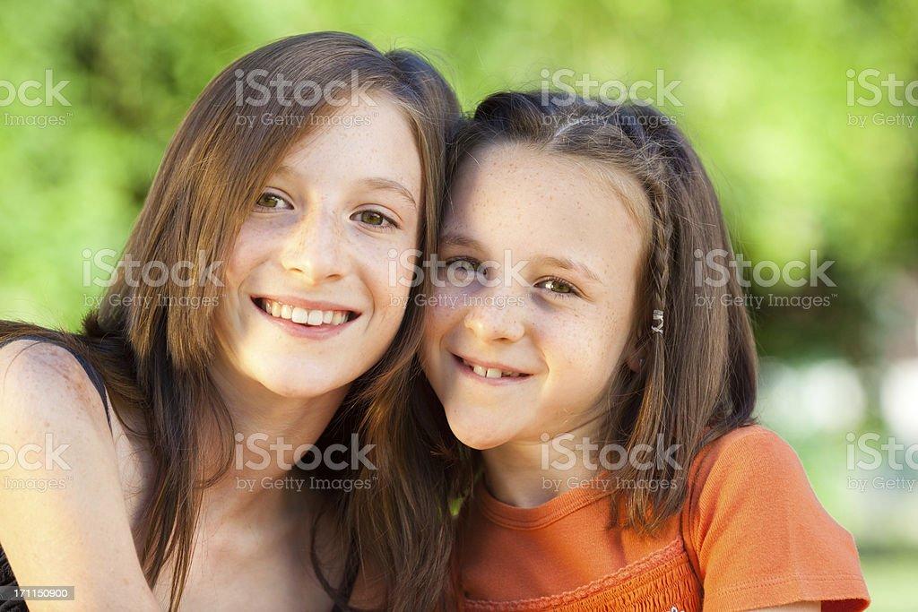 beautiful sisters hug posing at park outdoor stock photo