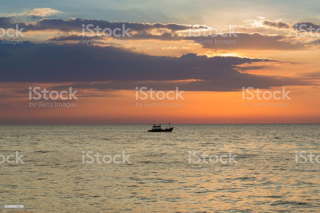 Beautiful sky during sunset over fishing boat stock photo