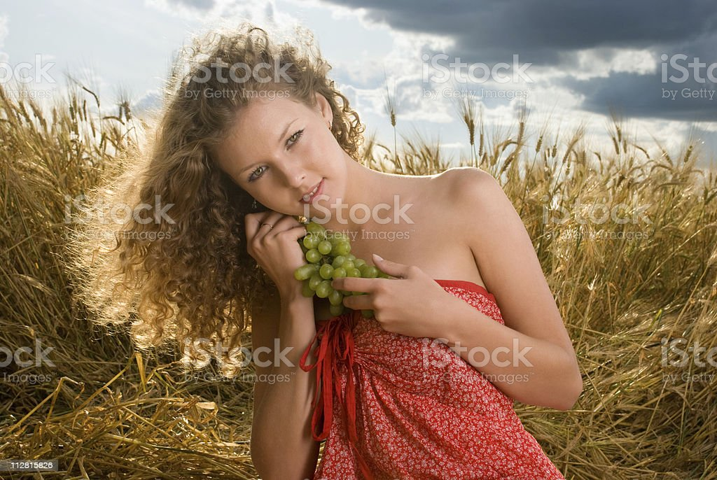 Beautiful slavonic girl on picnic in wheat field with grapes royalty-free stock photo