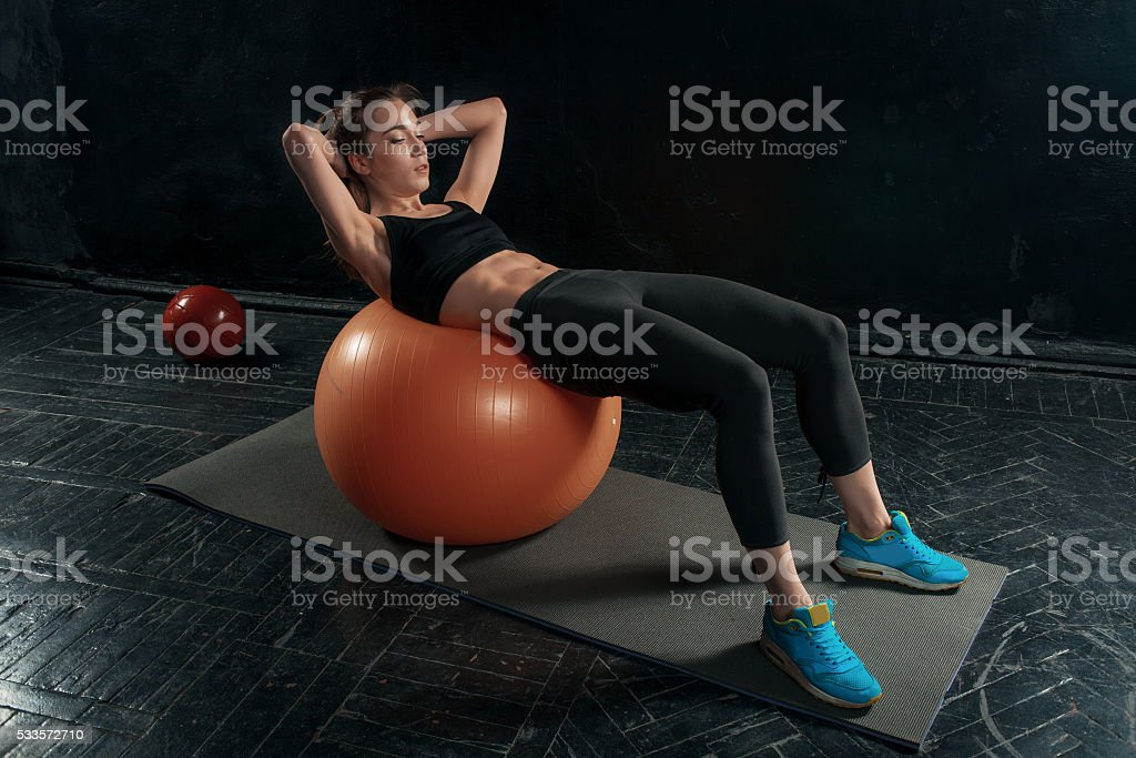 Beautiful slim brunette doing some gymnastics at the gym stock photo