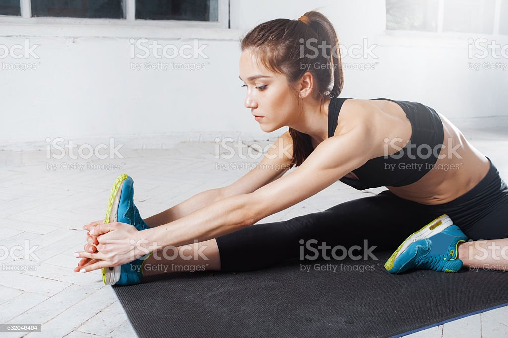 Beautiful slim brunette  doing some stretching exercises in a gym stock photo