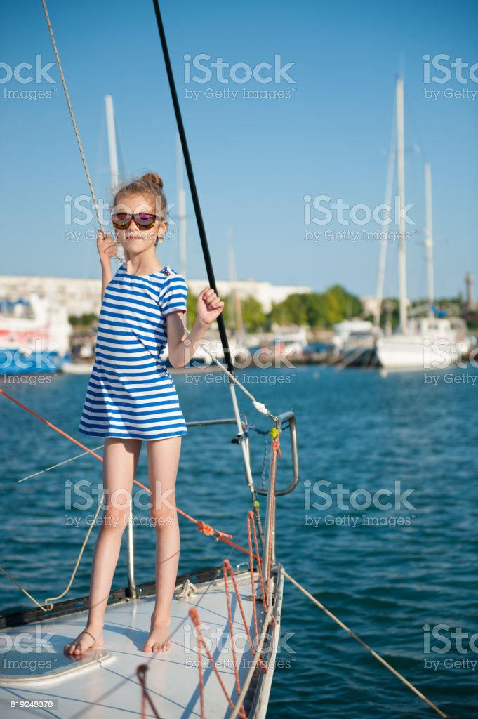 beautiful slim little girl in a striped shirt and sunglasses on luxury yacht in summer day stock photo