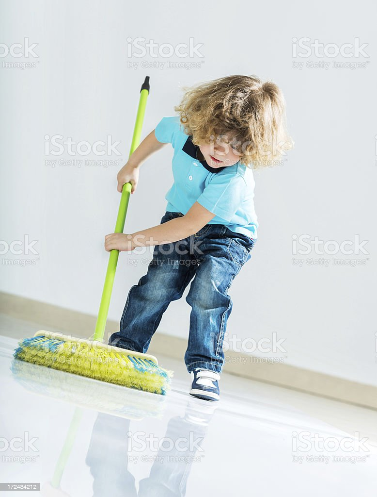 Beautiful small boy cleaning the floor. stock photo
