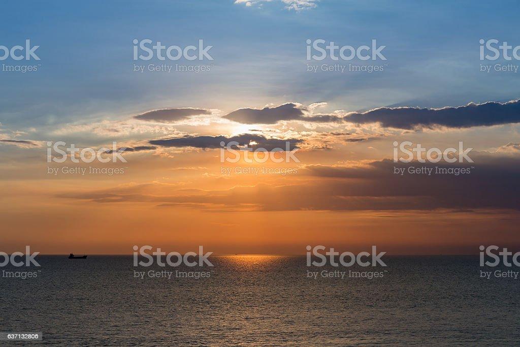Beautiful Small fishing boat over sunset seacoast skyline stock photo