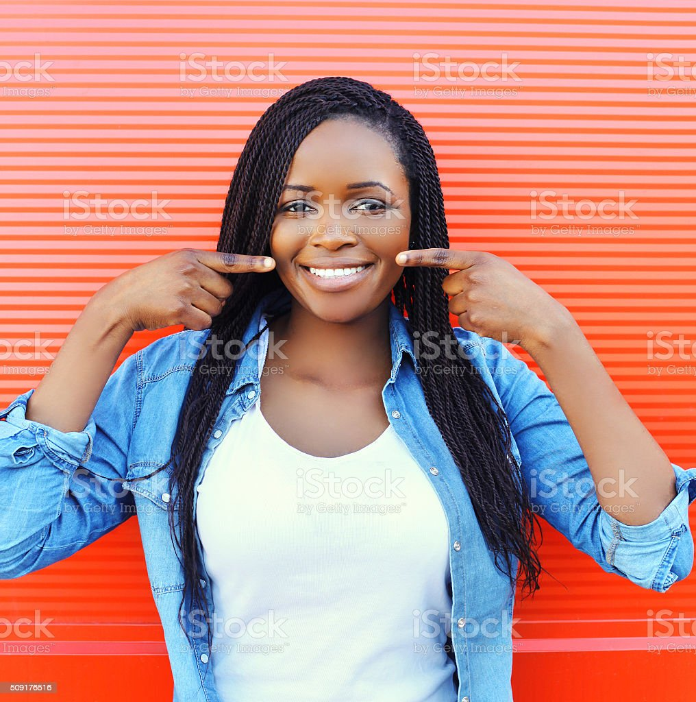 Beautiful smiling african woman showing fingers on teeth stock photo