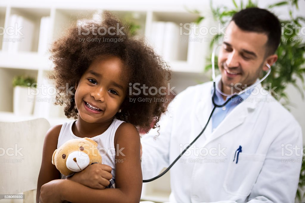 Beautiful smiling afro-american girl with her pediatrician stock photo