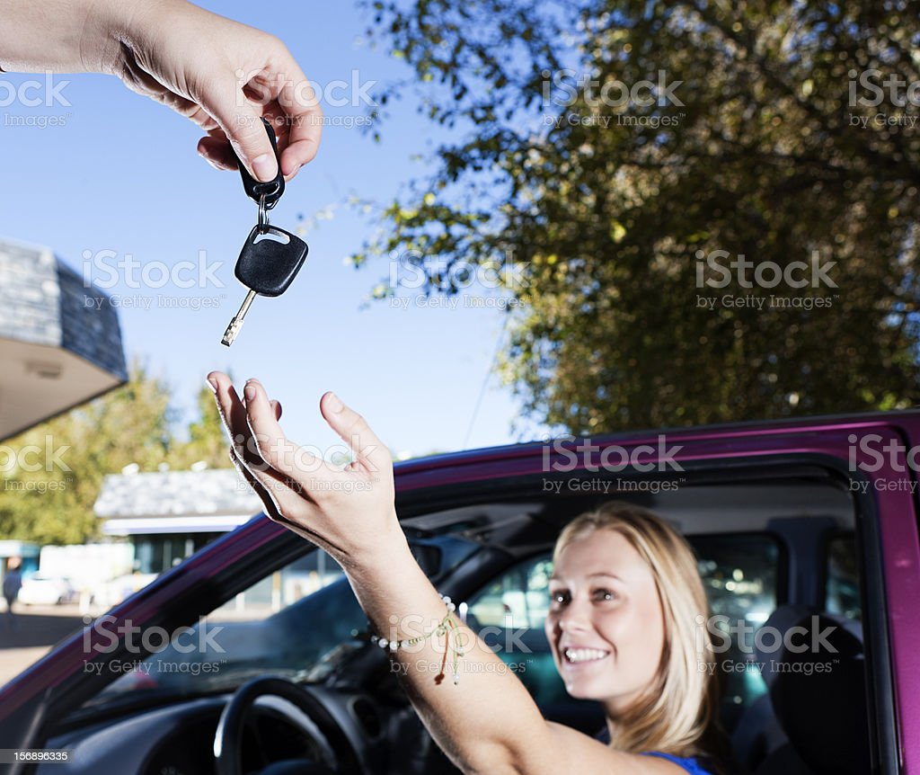 Beautiful smiling blonde being given keys to her vehicle royalty-free stock photo