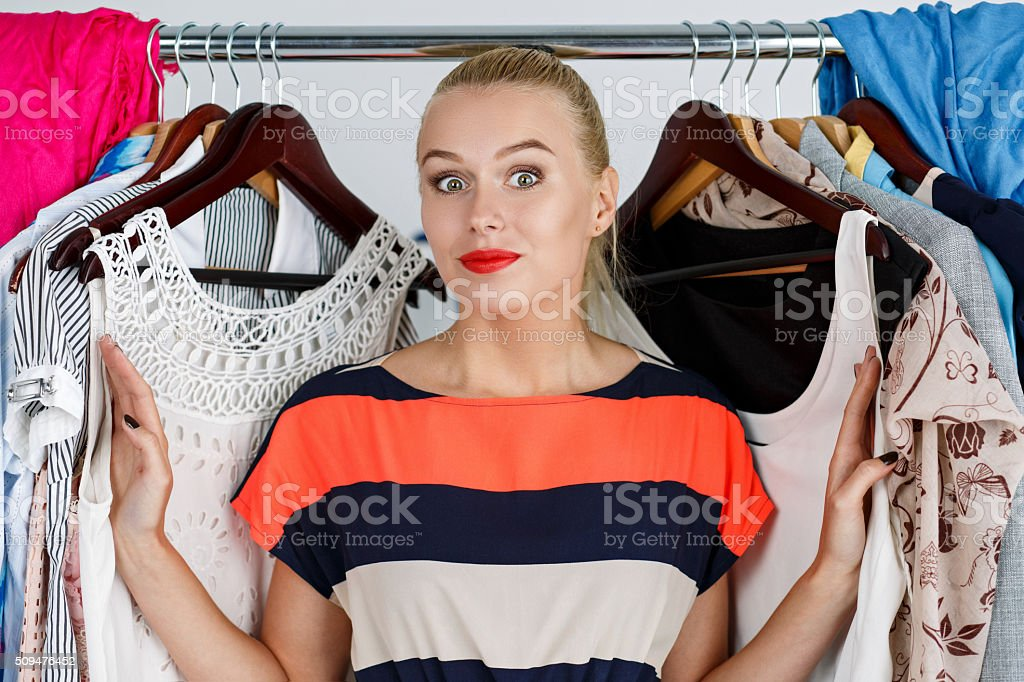 Beautiful smiling blonde woman standing inside wardrobe rack ful stock photo