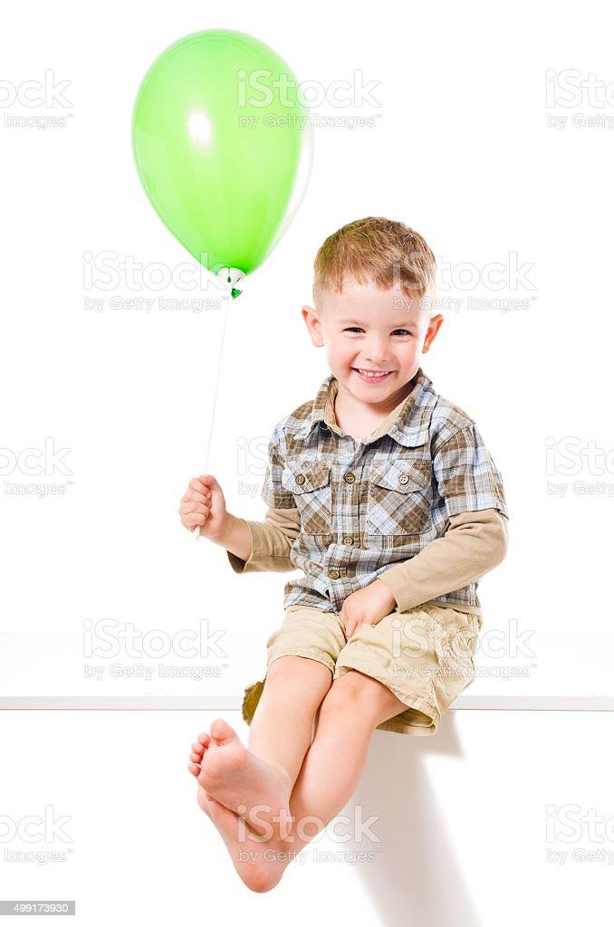 Beautiful  smiling boy sitting with balloon stock photo