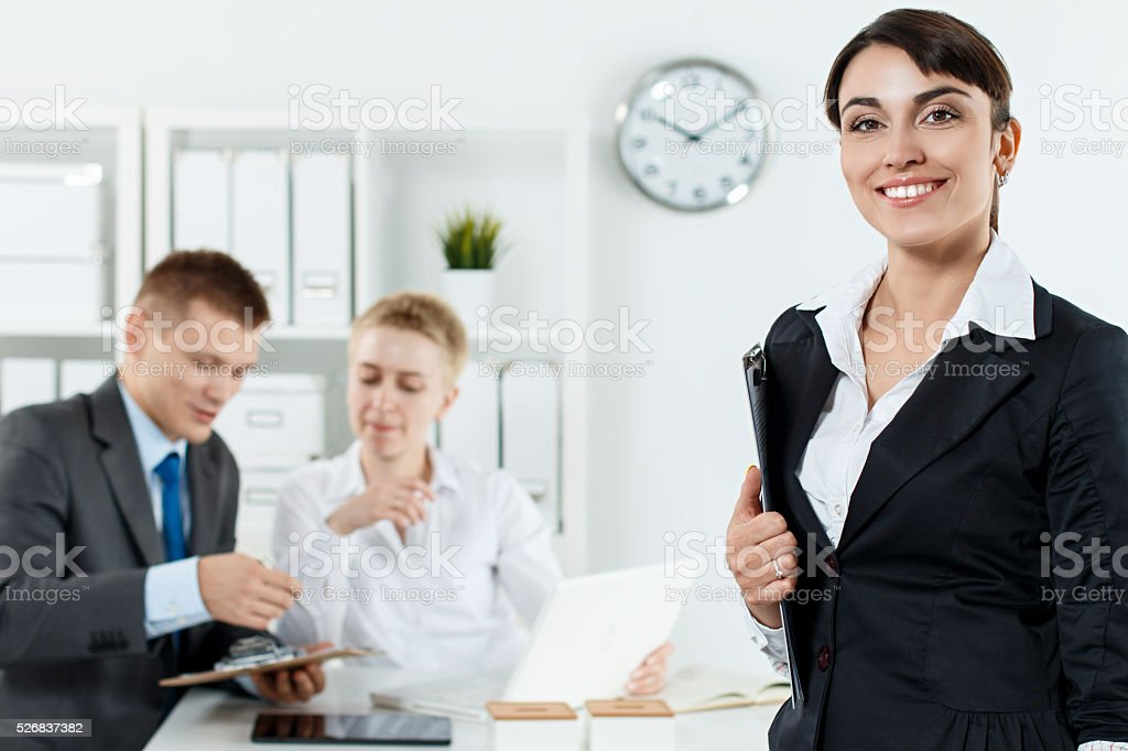 Beautiful smiling business woman in suit holding clipboard in ha stock photo