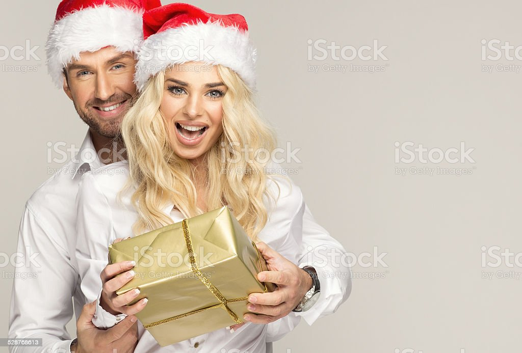Beautiful smiling couple in santa claus hats with presents stock photo