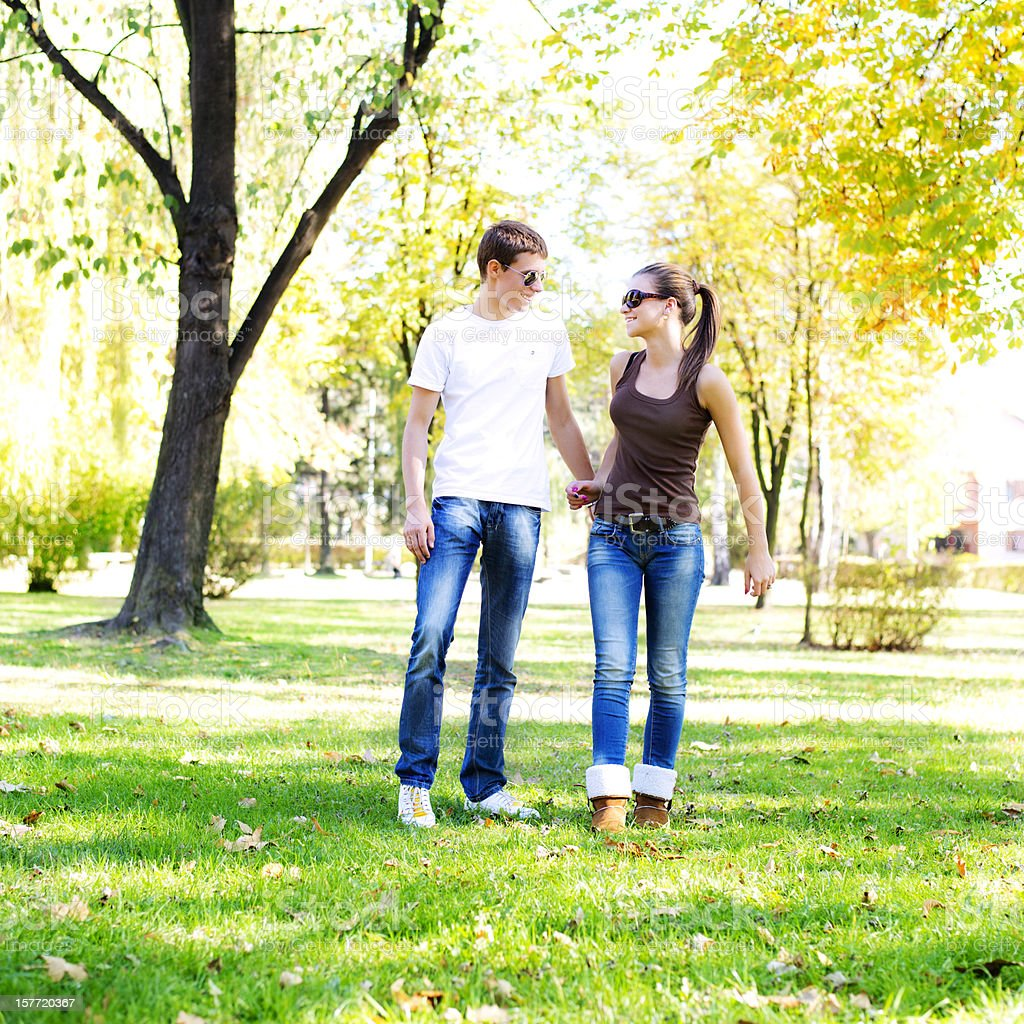Beautiful smiling couple walking in the park royalty-free stock photo