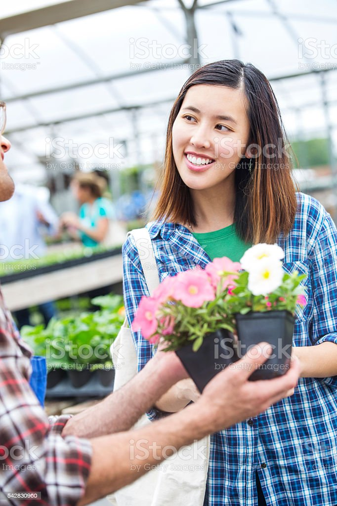 Beautiful smiling customer picking out flowers in a greenhouse stock photo
