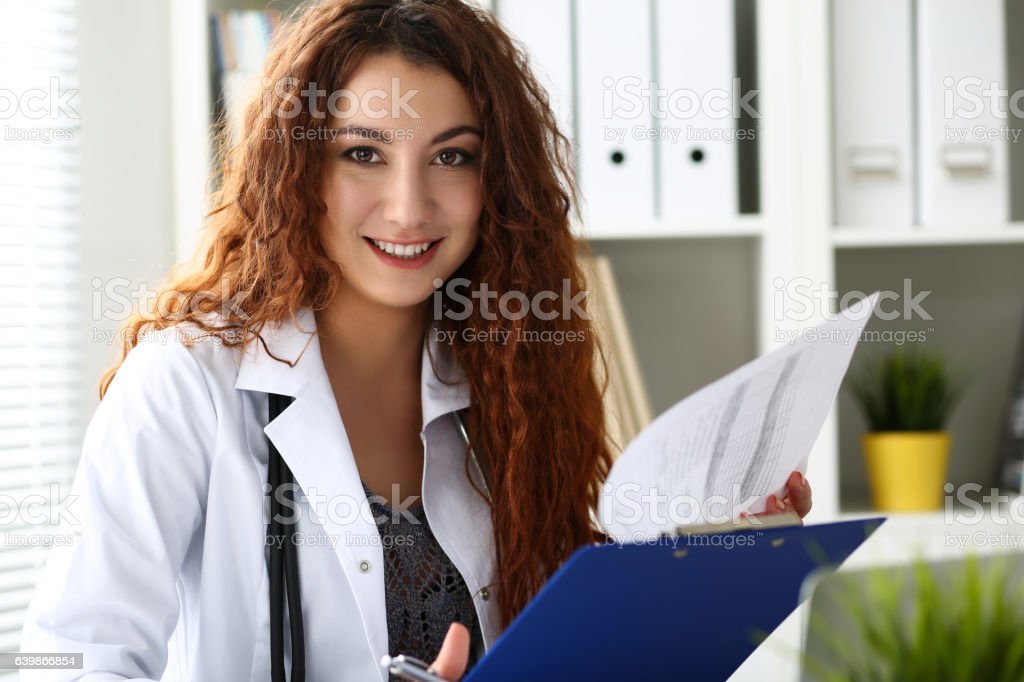 Beautiful smiling female doctor hold clipboard pad stock photo
