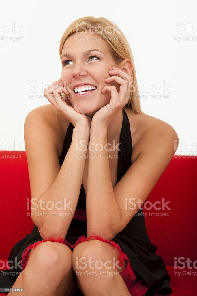 Beautiful smiling female sitting on a red sofa royalty-free stock photo
