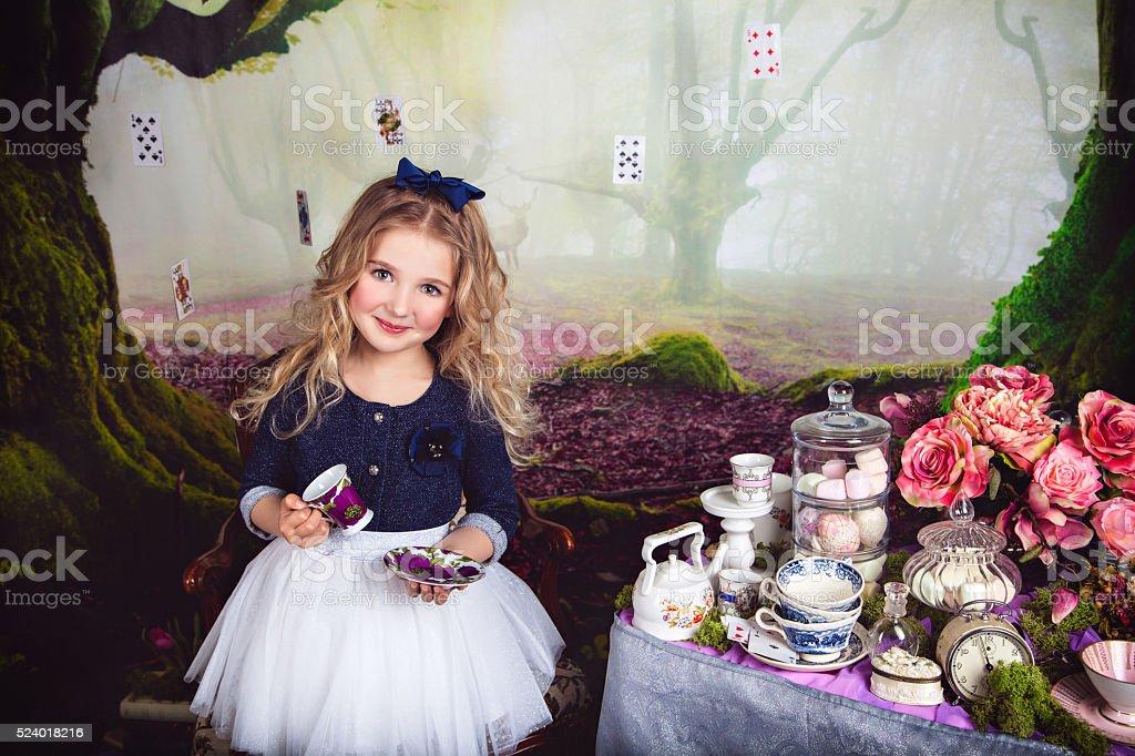 Beautiful smiling girl as Alice in Wonderland stock photo