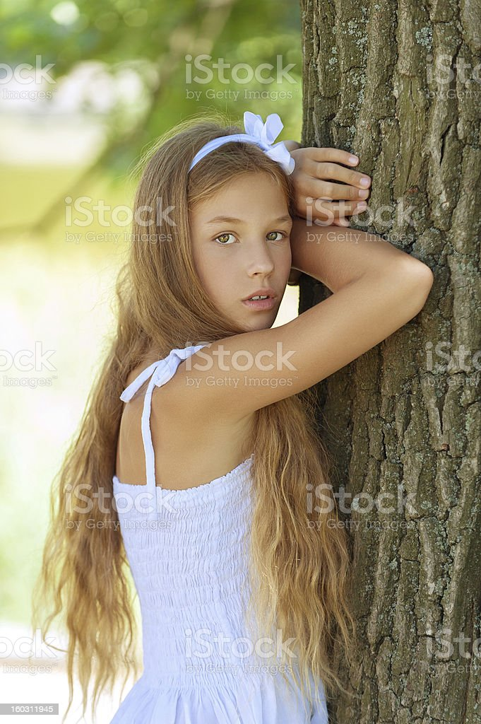 beautiful smiling girl near large tree royalty-free stock photo