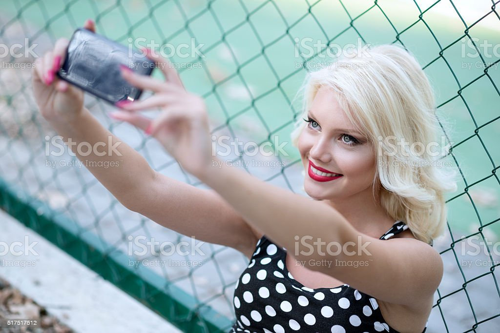 Beautiful Smiling Girl Taking Selfie with Smartphone Outdoor in Park stock photo