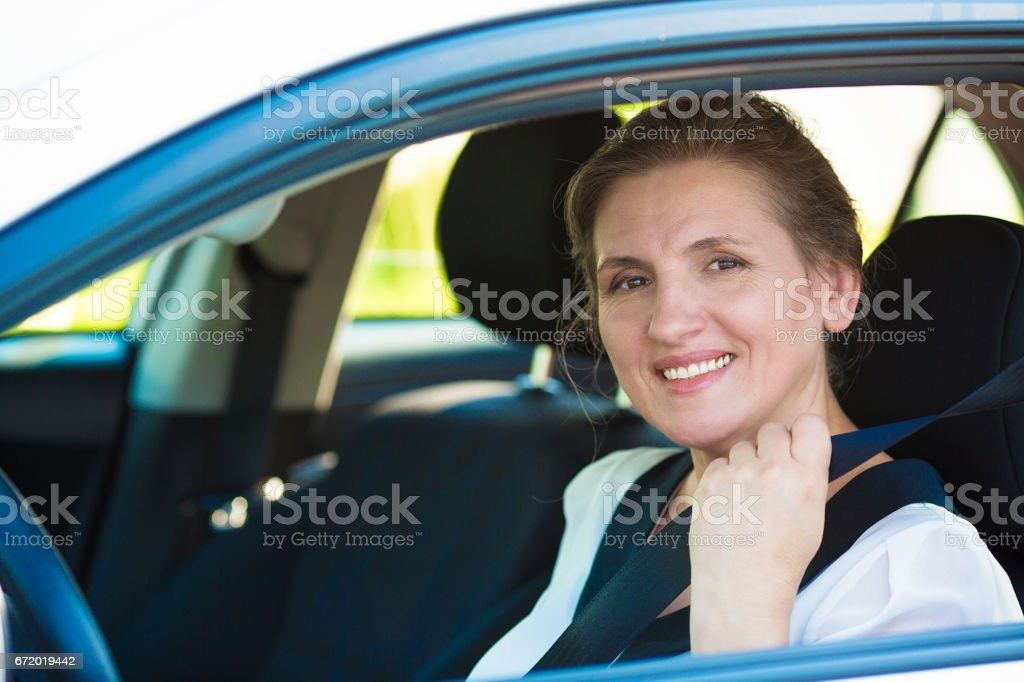 beautiful, smiling, happy, attractive woman pulling on seatbelt inside white car stock photo