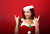 Beautiful smiling happy casual woman in santa clause costume sho