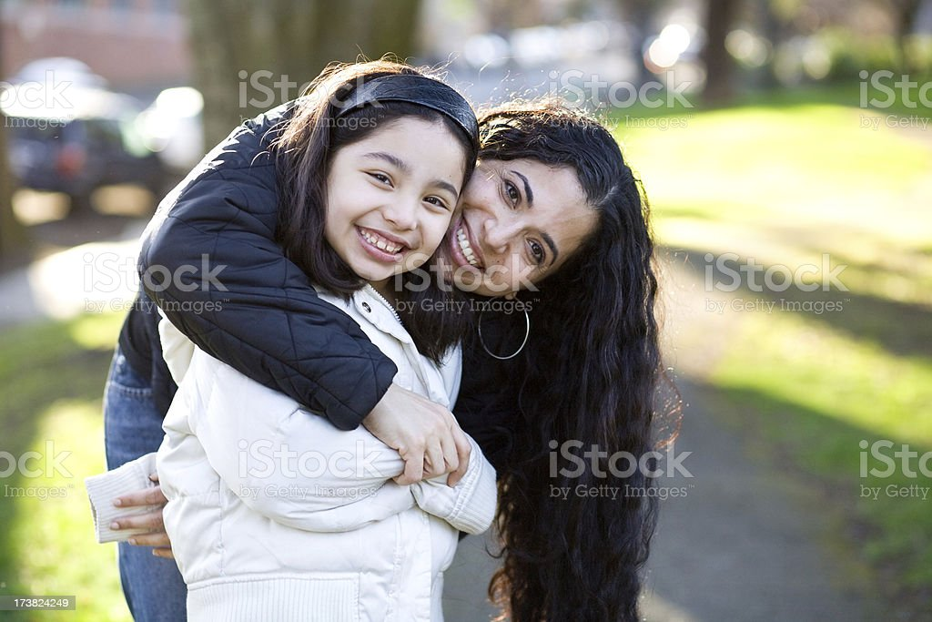 beautiful smiling hispanic mother and daughter hugging in a park royalty-free stock photo