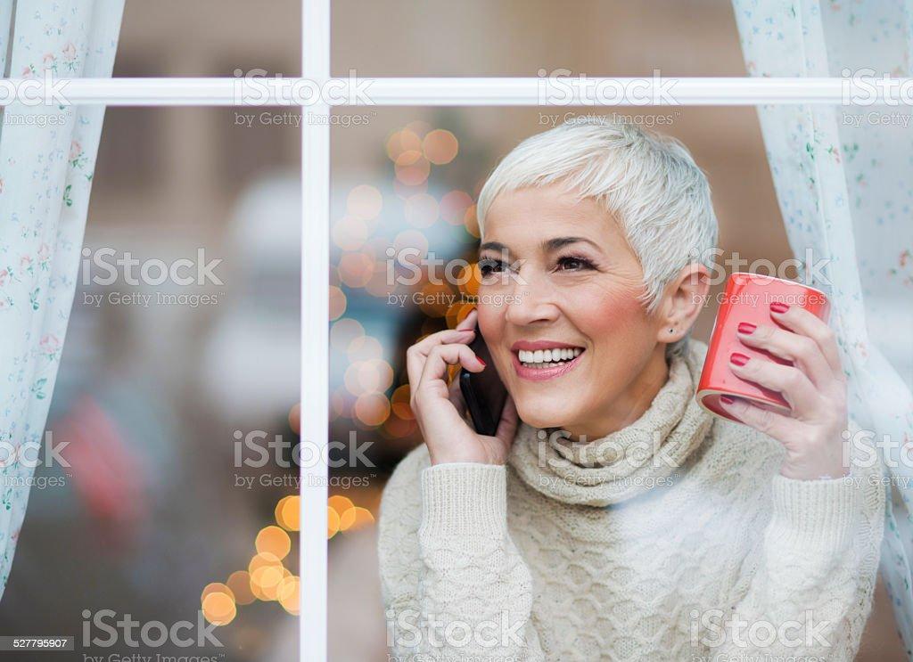 Beautiful smiling mature woman looking through window stock photo